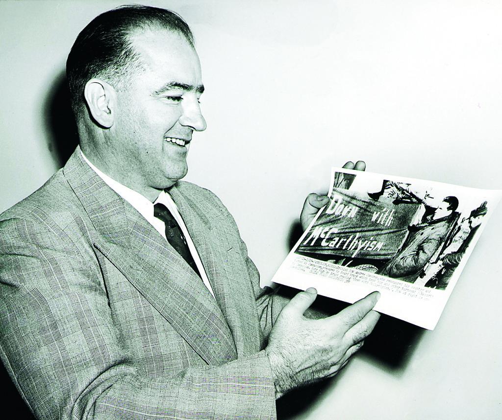 """Senator Joseph R McCarthy tittar på ett foto av kommunisten Andrew Condron framför en bil med banderollen""""Down with McCarthyism"""". År 1954. Foto: UPI / TT"""