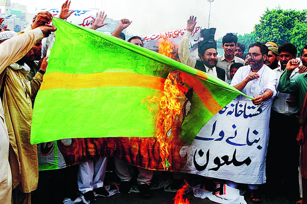 Pakistanska demonstranter bränner en gröngul svensk flagga 2006. Foto: K.M. Chaudary / SCANPIX