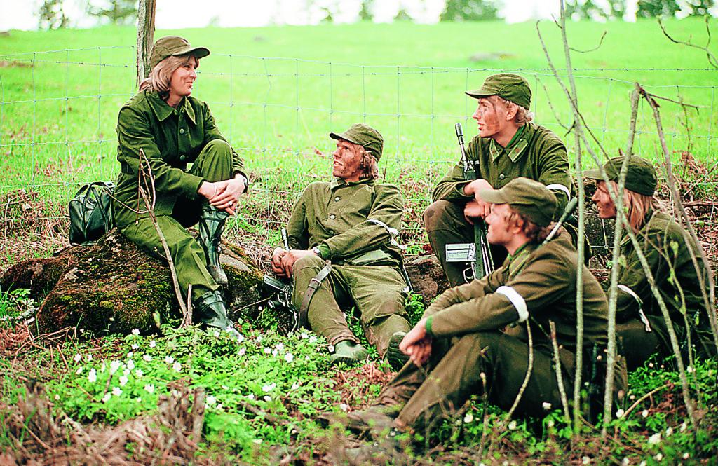 Fikapaus i gröngräset, en kvinnlig personalassistent samtalar med värnpliktiga soldater. Året är 1976. Foto: TT Nyhetsbyrån